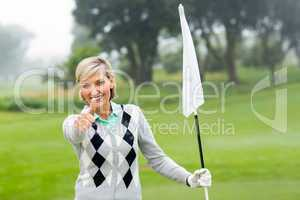 Lady golfer holding flag