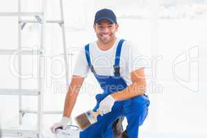 Handyman with paintbrush and can at home