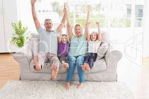 Family of four with arms raised sitting on sofa