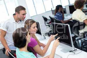 Computer teacher helping pretty female students