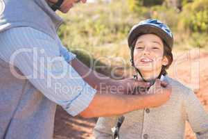 Father clipping on sons helmet