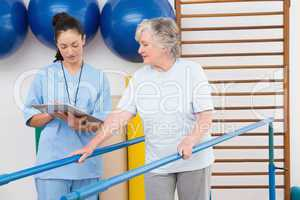 Senior woman walking with parallel bars with therapist