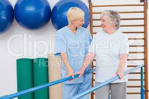 Therapist helping senior woman to walk with parallel bars