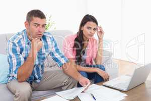 Couple calculating home finances together in house
