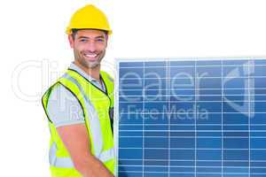 Smiling handyman in protective clothing carrying solar panel