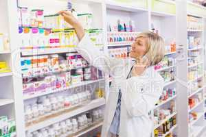 Smiling pharmacist phoning and taking medicine from shelf