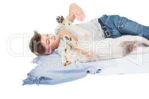 Boy playing with dog while lying on blanket