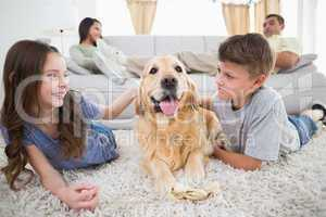 Siblings stroking dog on rug while parents relaxing on sofa