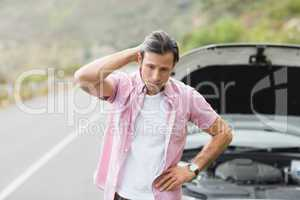 Stressed man waiting assistance after a car breakdown