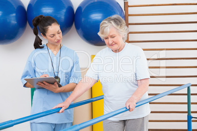 Therapist looking senior woman walking with parallel bars