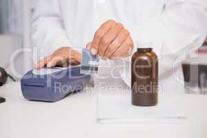 Pharmacist using keypad with credit card