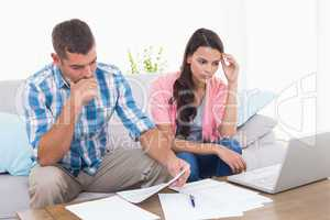 Stressed couple calculating home finances