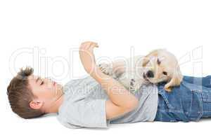 Puppy playing on boy lying over white background