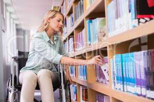 Smiling disabled student in library picking book