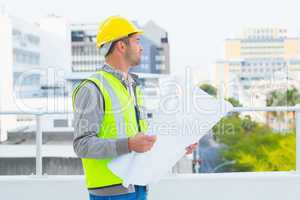 Architect in protective workwear holding blueprints outdoors