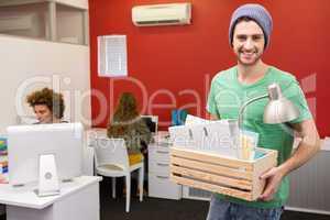 Casual businessman carrying his belongings in box