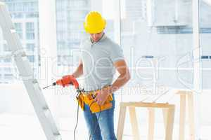 Repairman with drill machine in building