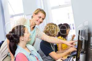 Computer teacher helping female students