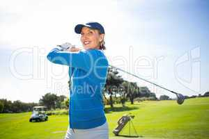 Lady golfer teeing off and smiling