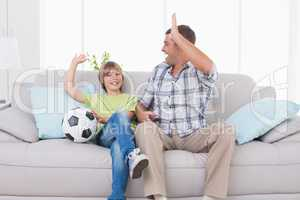 Father and son giving high-five while watching soccer match