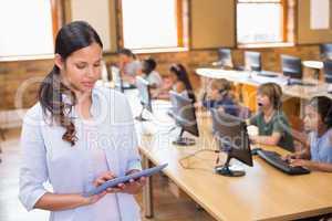 Pretty teacher using tablet computer in computer class