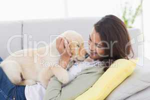 Woman playing with puppy while lying on sofa