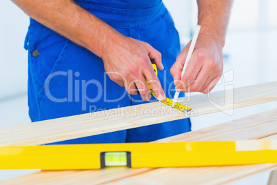Carpenter marking on plank with tape measure