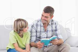 Happy father reading story for boy on sofa