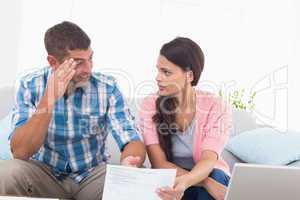 Stressed couple discussing over home finances