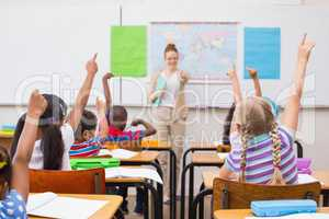 Pupils raising hand during geography lesson in classroom