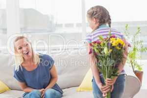 Surprise mother looking at girl hiding bouquet