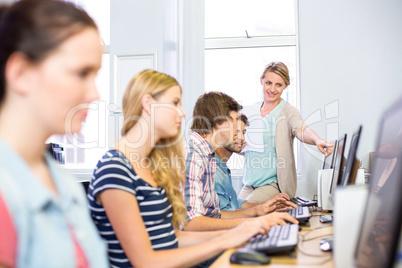 Computer teacher helping students