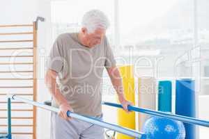 Senior man walking with parallel bars