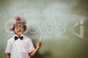 Boy dressed as senior teacher in front of blackboard