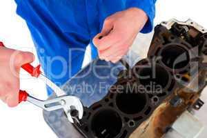 Male mechanic repairing car engine