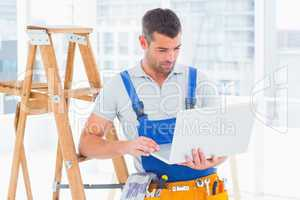 Repairman using laptop by ladder in office
