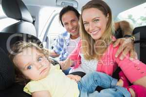 Parents securing baby in the car seat