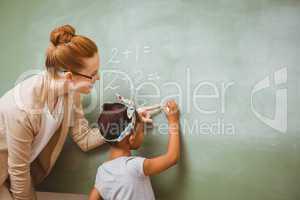 Teacher assisting girl to write on blackboard in classroom