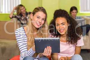 Young women using digital tablet in office