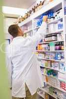 Pharmacist in lab coat taking jar from shelf