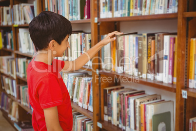 Side view of boy selecting book in library