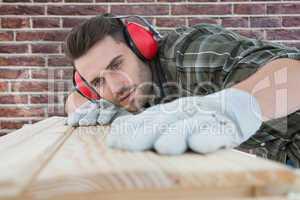 Composite image of carpenter measuring wooden plank
