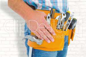Composite image of midsection of handyman wearing tool belt