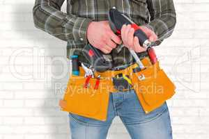 Composite image of manual worker holding gloves and hammer power