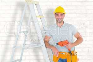 Composite image of happy handyman with power drill leaning on la