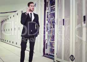 Composite image of serious businessman hand in pocket phoning