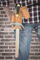 Composite image of cropped image of handyman wearing tool belt