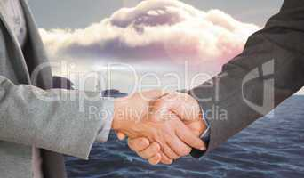 Composite image of two people having a handshake in an office
