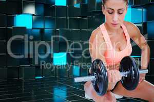 Composite image of strong woman doing bicep curl with large dumb