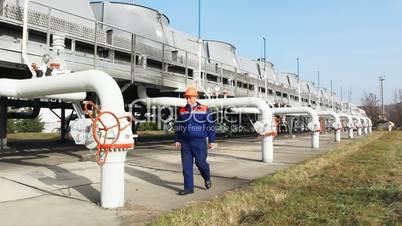 Worker closes valve on compressor station